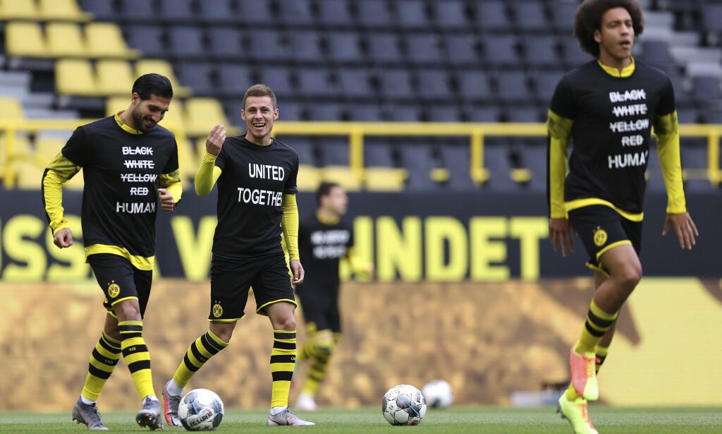 MARKERING: Borussia Dortmunds spillere varmer opp med antirasistiske budskap på trøyene før seriekampen mot Hertha Berlin lørdag. Foto: Lars Baron, Pool via AP / NTB scanpix