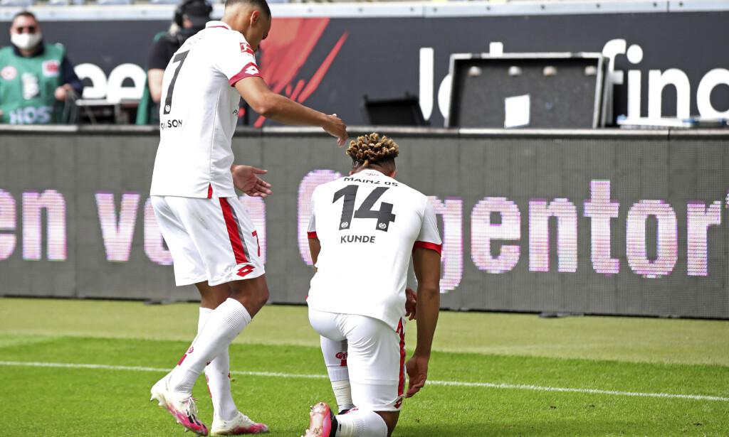 NED PÅ KNE: Mainz-spiller Pierre Kunde går ned på kne etter å ha scoret i borteseieren mot Eintracht Frankfurt lørdag, en av mange antirasistiske markeringer på tyske fotballarenaer i helgen. Foto: Alexander Hassenstein, Pool via AP / NTB scanpix