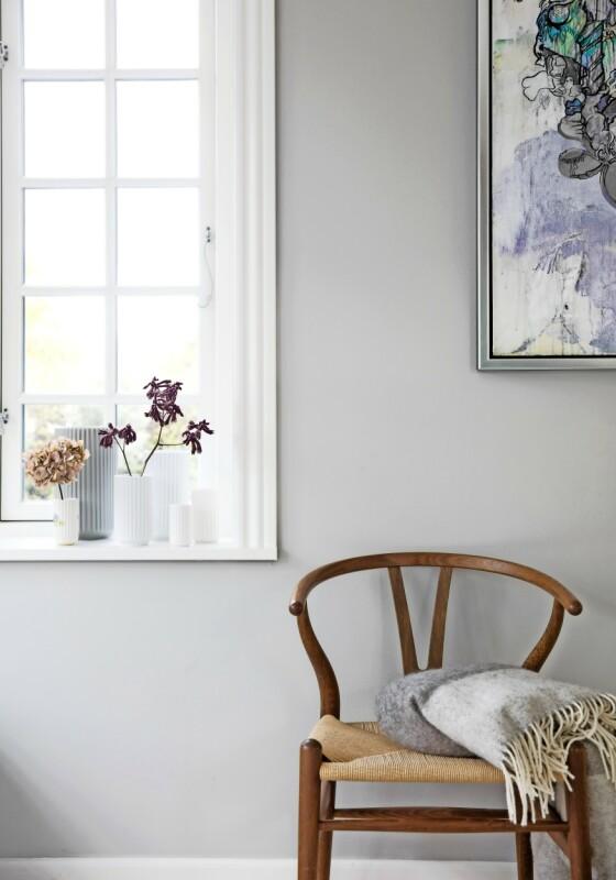 Y-stolen gir en varm kontrast til den grå veggen. I vinduet står Kathrines samling av Lyngby-vaser. Tips! Plasser vaser fra samme serie, men i forskjellige størrelser, sammen i en gruppe. Det gir ro og liv på en gang. FOTO: Kira Brandt