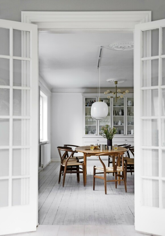 Spisebordet og stolene er designet av Hans   J. Wegner, og skapet er bygget av en snekker. Tips! Møbler i tre gir varme til et rom som er malt i en enkel, kjølig farge. FOTO: Kira Brandt