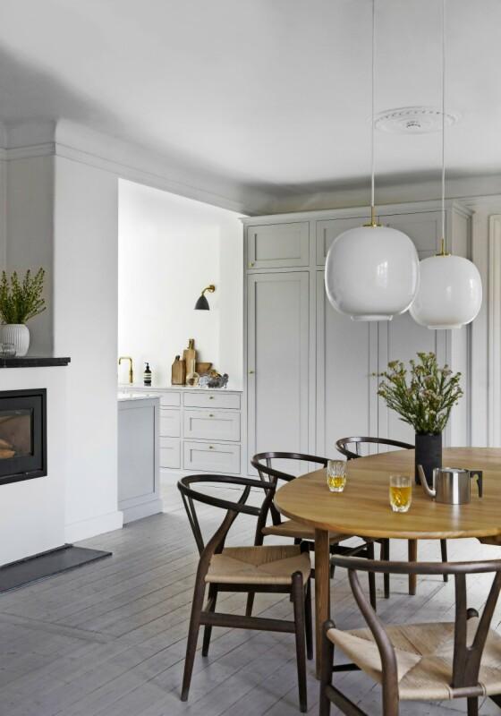 Kjøkkenskapene fortsetter fra det lille åpne kjøkkenet og inn i spisestuen, der de er i høy versjon. Det får rommene til å henge fint sammen – og gir godt med skapplass. Radiohus-pendel- lampene fås ny fra Louis Poulsen. FOTO: Kira Brandt
