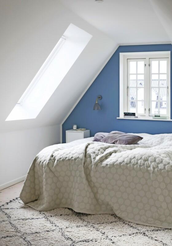 Kathrine synes at blåfargen gir en rolig stemning, og hun har derfor malt endeveggen på soverommet blå. Lampen er fra Bestlite og sengeteppet fra Hay. Tips! En vegg malt i en annen farge enn resten av rommet gir ofte en spennende effekt. FOTO: Kira Brandt