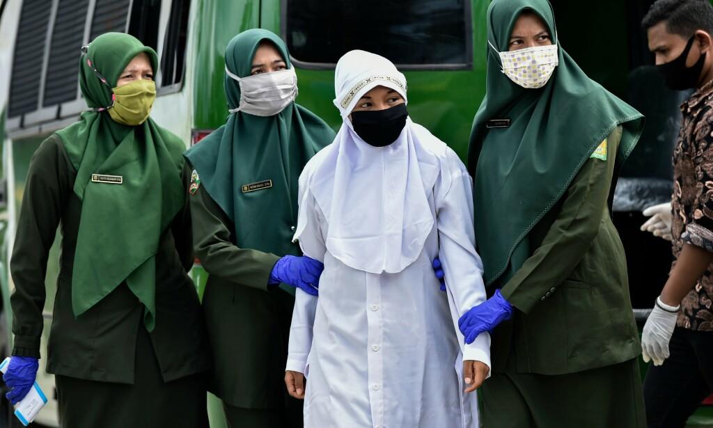 FØLGES: Her følges kvinnen ut foran moskeen, hvor hun senere ble pisket ett hundre ganger. Foto: NTB Scanpix