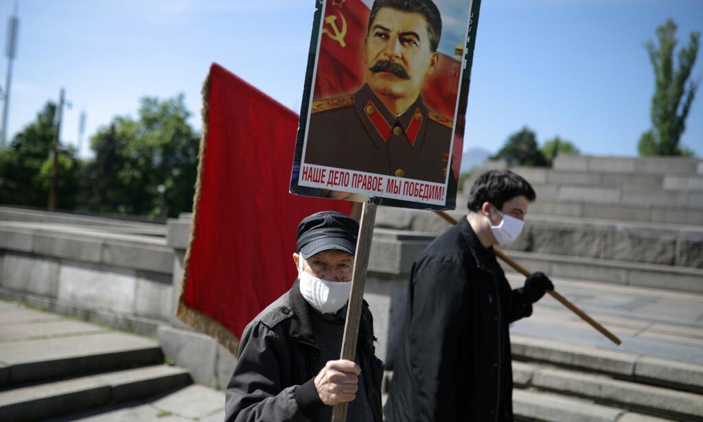 ANNET PERSPEKTIV: Oppveksten i et diktatur som lot som det var kommunistisk, og etter 1989 i et konkursbo som lot som det var demokratisk, har satt sine spor hos bulgareren Ivan Krastev. I en ny bok diskuterer han hvilke konsekvenser covid-19 vil få for verdenssamfunnet. Bildet viser en mann med Josef Stalin-plakat, under en markering av frigjøringsdagen i den bulgarske hovedstaden 9. mai i år. Foto: NTB SCANPIX / REUTERS/Stoyan Nenov