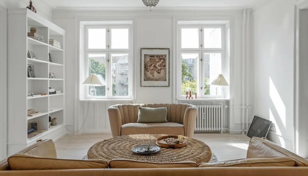 Kurvmøbler var mye brukt på 1980-tallet, og nå er de tilbake for fullt. Nøy deg gjerne med ett enkelt kurvmøbel for å tilføre rommet litt natur. Innred de midterste rommene med en form for symmetri som her, der sofabordet står midt foran de åpne dobbeltdørene. Slik får øyet ro. FOTO: Peter Kragballe og Christoffer Turell