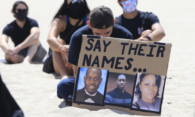 MISTET LIVET: Plakaten viser Ahmaud Arbery, George Floyd og Breonna Taylor. Demonstranter avbildet under et øyeblikks stillhet under en Black Lives Matter-demonstrasjon i Los Angeles 12. juni. Foto: AP / NTB Scanpix