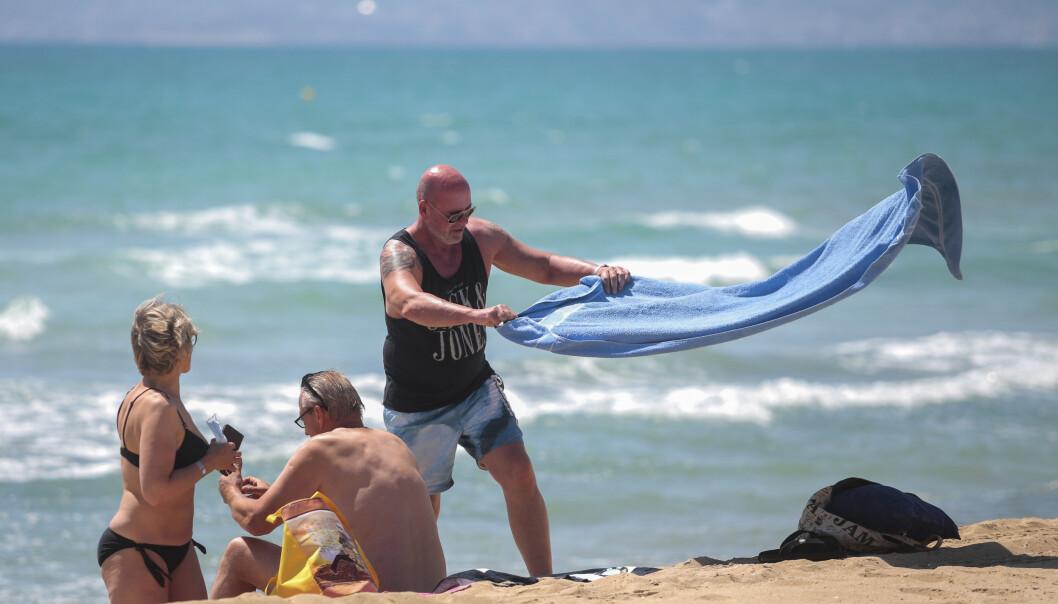 <strong>STRANDLIV:</strong> Tyske turister slenger seg ned på stranda i Palma de Mallorca i Spania mandag. Foto: Joan Mateu / AP / NTB Scanpix