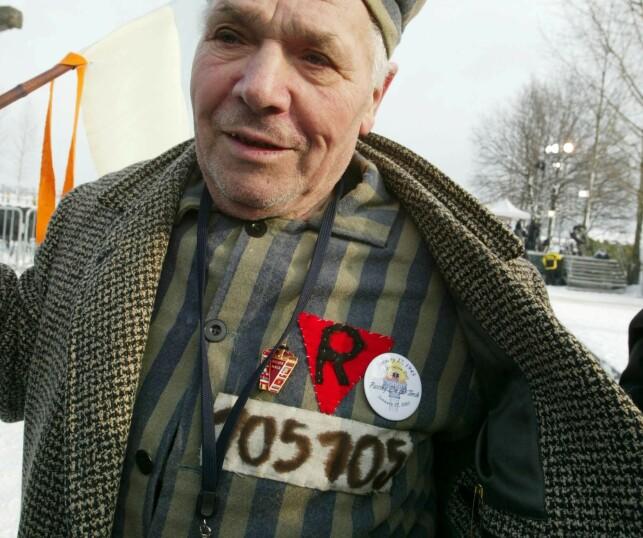 2005: En tidligere fange deltok i en seremoni i en etterligning av en fangedrakt på 60-års dagen for frigjøringen av Auschwitz Birkenau konsentrasjonsleir i Polen. Her kan man se den røde trekanten på brystet. Foto: REX
