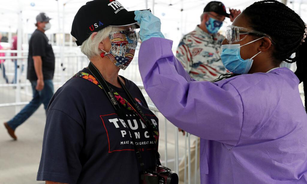 SJEKKES: Her sjekkes temperaturen til en Trump-supporter iført munnbind. Foto: REUTERS/Shannon Stapleton
