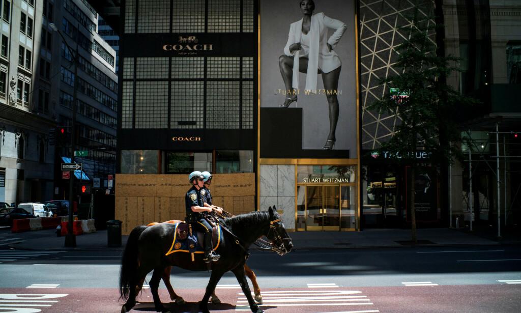 ÅPNER OPP: Ytterligere 1,48 millioner amerikanere meldte seg arbeidsledige sist uke, et fall fra uka før. Bildet viser to politibetjenter til hest på 5th Avenue i New York, samme dag som enkelte butikker åpnet opp igjen 12. juni. Foto: Eduardo Munoz   / Reuters / NTB Scanpix