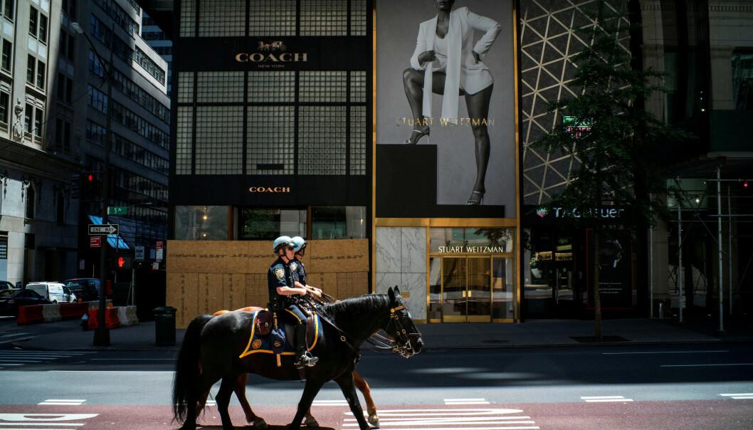 <strong>ÅPNER OPP:</strong> Ytterligere 1,48 millioner amerikanere meldte seg arbeidsledige sist uke, et fall fra uka før. Bildet viser to politibetjenter til hest på 5th Avenue i New York, samme dag som enkelte butikker åpnet opp igjen 12. juni. Foto: Eduardo Munoz   / Reuters / NTB Scanpix