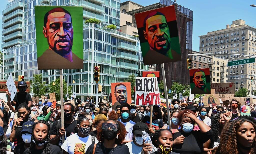 FLOYD: Demonstranter holder opp bilder av George Floyd under en demonstrasjon i New York City 19. juni. Foto: AFP