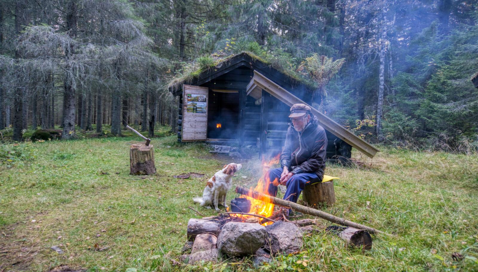 Grusetsetra i Maliskjæra naturreservat i Grue kommune i Hedmark hadde fast bosetting til midten av 1950-tallet. Nå er den vesle hytta med tilhørende gapahuk tilgjengelig for alle - helt gratis. Egil Skoglund venter på at bålkaffen skal bli klar. Ved siden av sitter hunden Atcho. Foto: Torkel Skoglund/Statskog