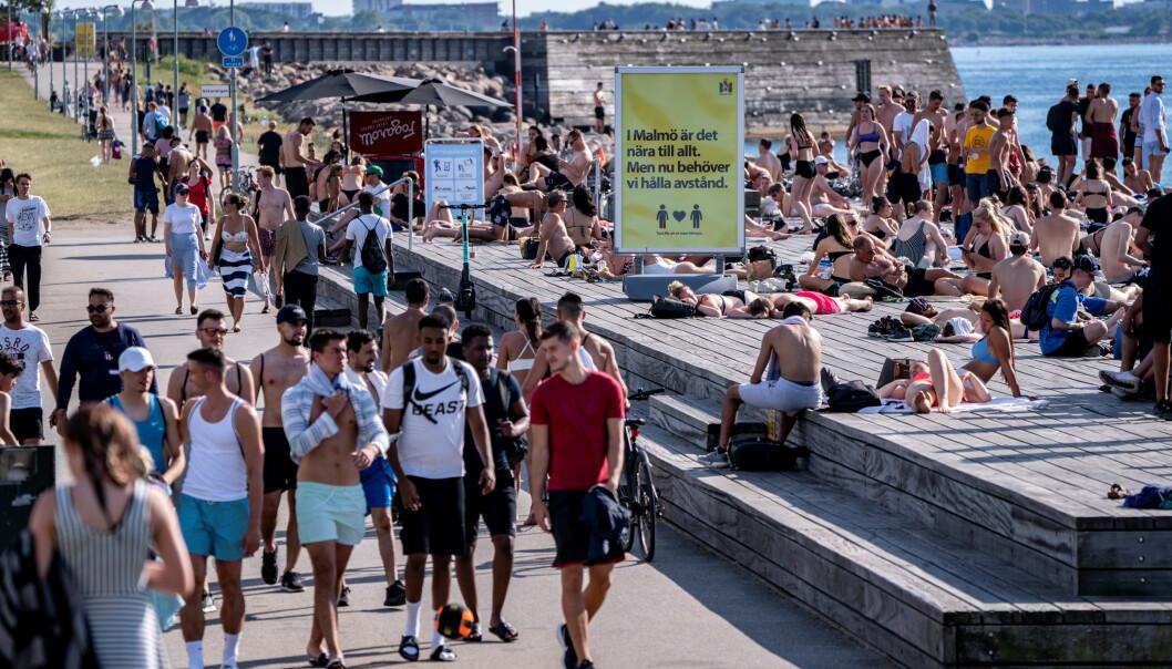 <strong>«HOLD AVSTAND»:</strong> Et skilt på en folksom badeplass i Malmö oppfordrer til å holde avstand. Bildet er tatt torsdag i forrige uke. Foto: Johan Nilsson / TT News Agency / REUTERS / NTB scanpix