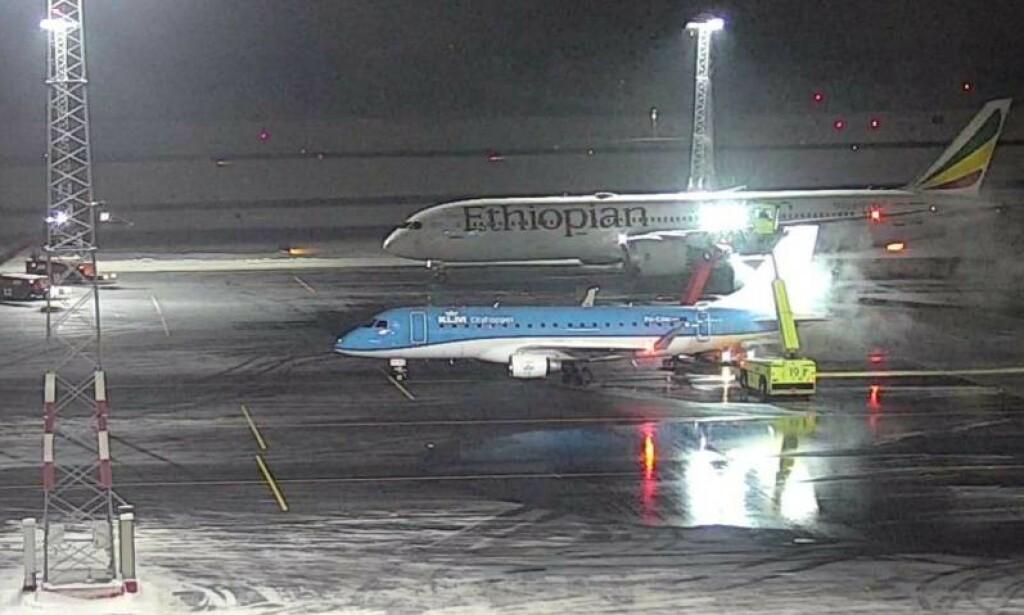 KOLLISJONSØYEBLIKKET: Bildet fra et overvåkingskamera er tatt idet ET-AUP krasjet med masta. Foran et fly som ER dimensjonert for avisingsplassen - et KLM Embraer 190. Foto: Avinor