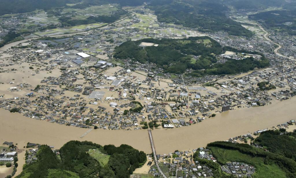 EVAKUERES: Om lag 200 000 innbyggere har fått ordre om å forlate hjemmene sine vest i Japan, der kraftig regn fører til flom og jordskred. Mange er isolert og 13 er savnet. Her ses elva Kuma sørvest i landet. Foto: Kyodo News via AP / NTB Scanpix