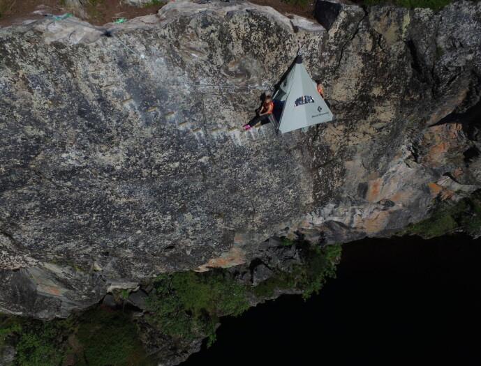SIKRING: Du må klatre ned til teltet for to, som henger midt i fjellveggen. Heldigvis blir du blir utstyrt med radioforbindelse til nattevakta i parken. FOTO: Rypetoppen Adventurepark