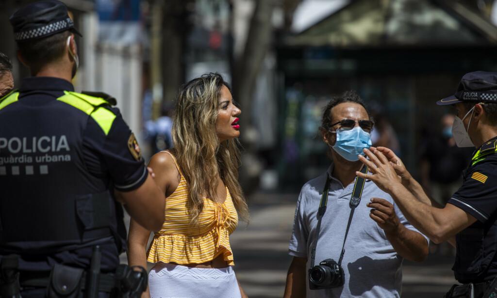 MUNNBIND: Politiet i Catalonia i Spania forklarer en dame at det påbudt med munnbind. Nå gjeninnføres det tiltak i regionen etter opplussing av smittetilfeller. Foto: AP Photo/Emilio Morenatti/NTB Scanpix