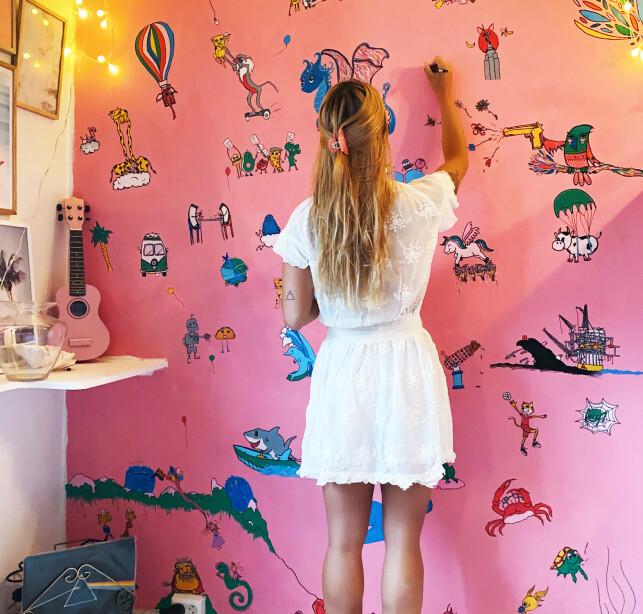 KREATIV: På en rosa vegg i leiligheten tegner hun, for å gjøre den mer personlig. Foto: Privat