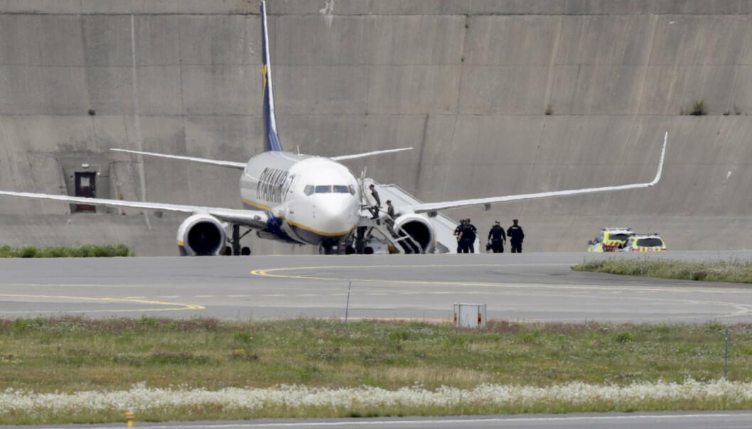 Politistyrker på vei inn i Ryanair-flyet fredag ettermiddag. Flyet ble undersøkt av politiets bombegruppe, men det ble ikke funnet noen bombe. Foto: Berit Roald / NTB scanpix