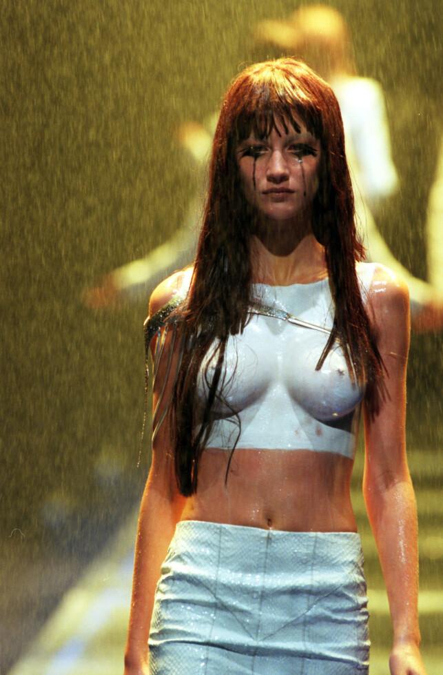 OPPSIKTSVEKKENDE: I 1998 trodde hun at hun skulle få en matchende topp til skjørtet sitt, da hun skulle gå for Alexander McQueen. Det fikk hun ikke. Da hun stilte seg på bakbeina, ble det bestemt at de i stedet skulle sminke på en hvit topp. Det har gått ned i motehistorien som et ikonisk øyeblikk. Foto: NTB Scanpix