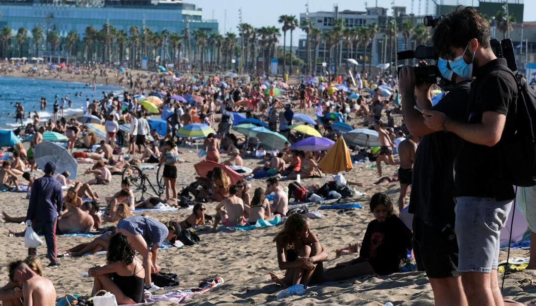 IGNORERTE OPPFORDRINGER: Svært mange mennesker benyttet søndagen til en tur på stranda Barceloneta i Barcelona søndag. Dette til tross for at myndighetene har bedt folk om å bli hjemme på grunn av økende smittetall. Foto: Nacho Doce / Reuters / NTB Scanpix