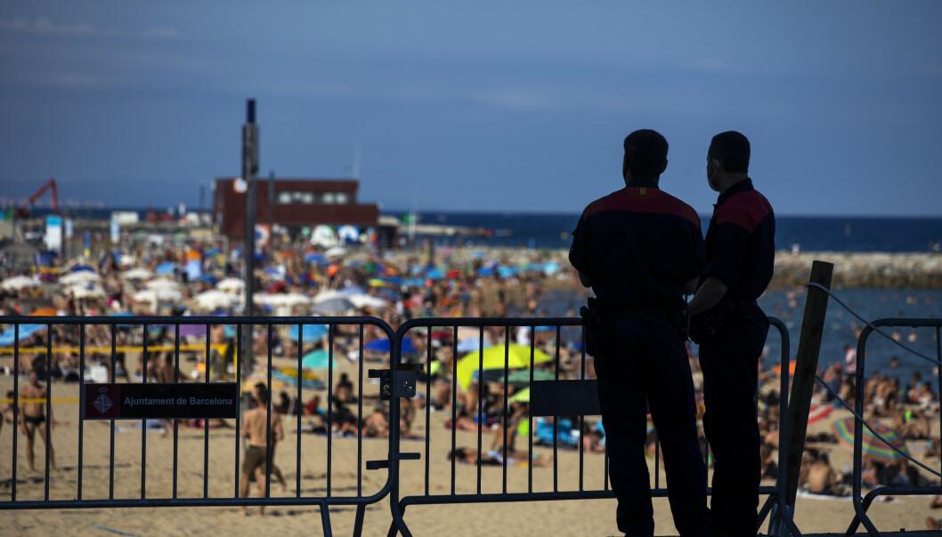 Politiet passer på at ikke flere personer bruker stranden i Barcelona. Til tross for at antallet tilfeller av korona i Nord-Spania øker, er det mange som ikke forholder seg til smittebegrensningstiltakene. Foto: Emilio Morenatti / AP / NTB scanpix