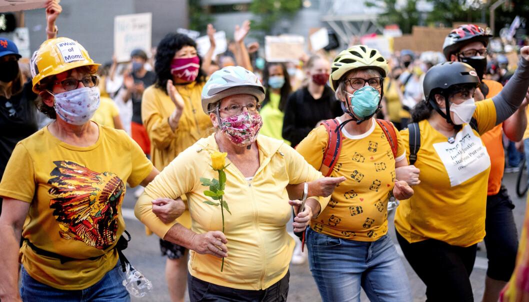 """WALL OF MOMS: Norma Lewis (med blomst) og andre demonstranter som kaller seg """"Wall of Moms"""" protesterer mot de føderale styrkene i Portland. Foto: AP Photo/Noah Berger"""