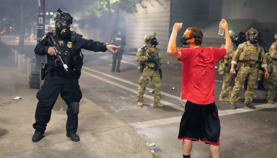 DEMONSTRASJONER: Føderale agenter og en demonstrant i Portland. Foto: Nathan Howard/Getty Images/AFP