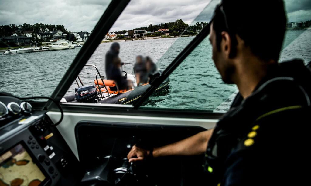 ULOVLIG KJØRING: Politibetjentene Øystein og Daniel stanser fire unge jenter og gutter i en 10-11 fots jolle. Båtføreren er 15 år og for ung til å kjøre selv. Foto: Christian Roth Christensen