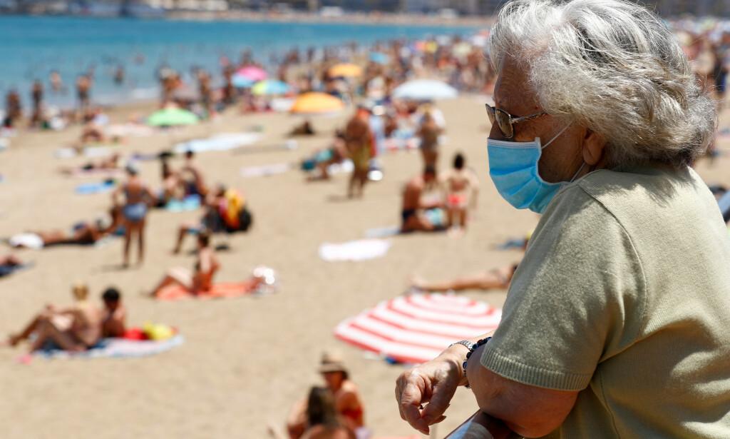 FORHOLDSREGLER: En eldre kvinne med munnbind på stranda Las Canteras på Gran Canaria. Foto: Borja Suarez / Reuters / NTB Scanpix