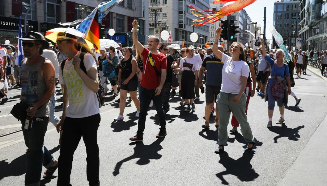 OPPRØRTE: Demonstrantene i Berlin mener koronafaren er sterkt overdrevet og er uenige i at det trengs strenge koronarestriksjoner. Enkelte hadde også med seg svenske flagg. Foto: Markus Schreiber / AP / NTB Scanpix