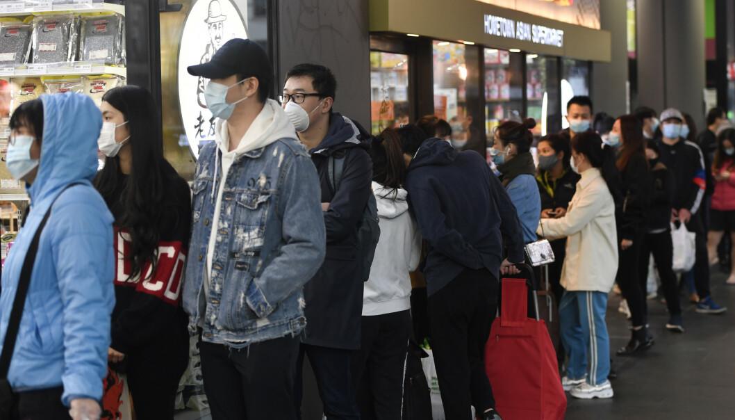 HAMSTREKØ: Folk står i kø utenfor et supermarked i Melbourne for å hamstre mat få timer før portforbudet trådte i kraft søndag kveld. Foto: Erik Anderson / AAP Image via AP / NTB Scanpix
