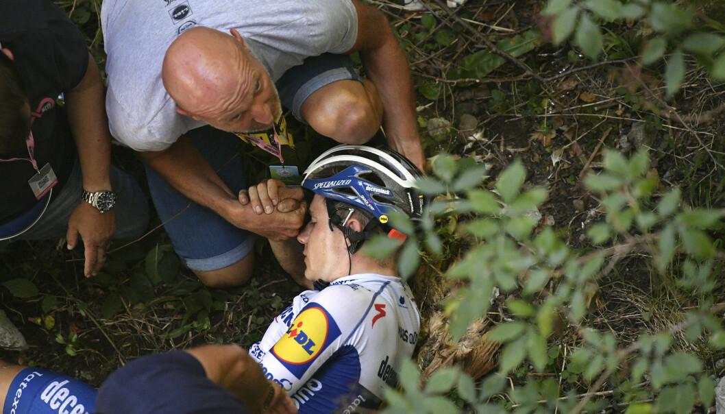Stjernesyklist Remco Evenepoel veltet stygt lørdag. Her mottar han hjelp i minuttene etterpå, før han ble fraktet til sykehus. Foto: Fabio Ferrari/LaPresse via AP / NTB scanpix