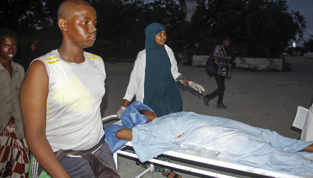 En såret kvinne blir hjulpet bort etter at et hotell i Somalias hovedstad Mogadishu ble angrepet søndag. Foto: Farah Abdi Warsameh/AP/ NTB Scanpix