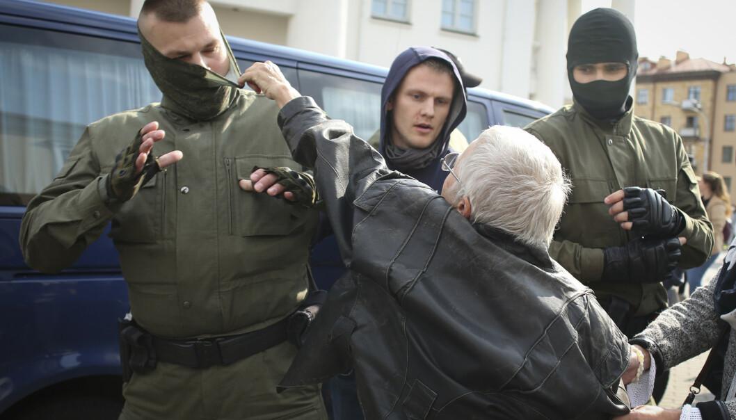 <strong>SAMMENSTØT:</strong> En eldre kvinne river ansiktsmasken av en politibetjent. Foto: NTB Scanpix.