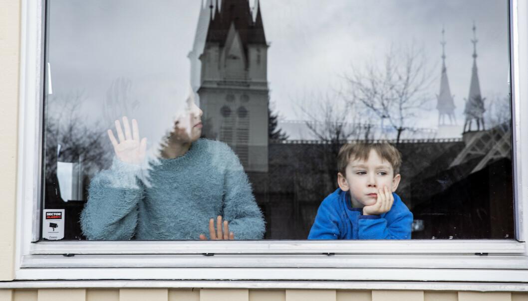 Unger holdes hjemme når skoler og barnehager holder stengt over hele lander på grunn av koronaviruset. På bildet Eivind (5) og Sigrid (10) som kjeder seg og ser ut av vinduet. Foto: Gorm Kallestad / NTB scanpix Modellklarert