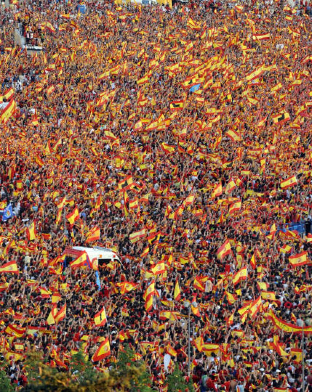 <strong>BLE HYLLET I GATENE:</strong> Hundretusener  av spanjoler var møtt fram da VM-vinnerne kjørte gjennom Madrids gater dagen etter 1-0-seieren mot Nederland. Foto: AFP PHOTO / DOMINIQUE FAGET