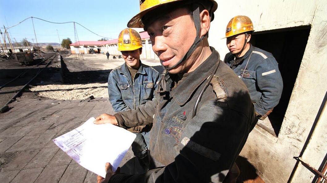 SIKKERHET: Zhang Chang Yi (43) viser oss sikkerhetsskjemaet gruvearbeiderne må krysse av på hver gang de skal ned i gruva. Arbeidskameratene Kang Mi Zhu (43) og Feng Qin Bao (40) står i bakgrunnen. Sikkerheten og betingelsene har blitt bedre i Wuhushan-gruva. I 1982 var månedslønna på snaue 80 kroner. I dag er den på omlag 2000 kroner. Foto: Kristoffer Egeberg