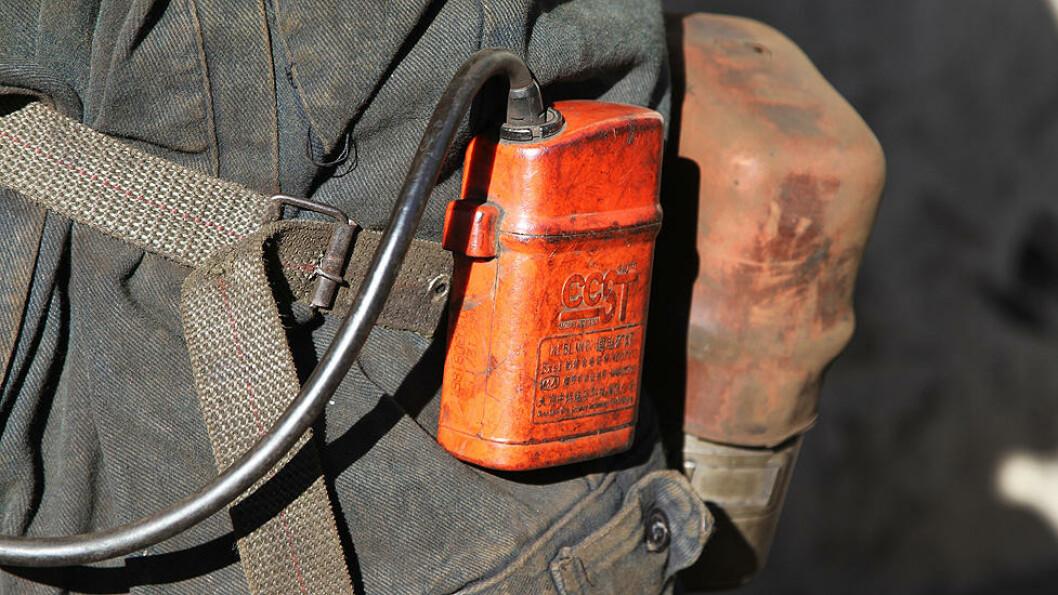 UTEN GNIST: På grunn av eksplosjonsfaren i gruva, må alt elektrisk utstyr være isolert. Dette er batteripakken til hodelykta. Bak henger beholderen til oksygenmasken. Foto: Kristoffer Egeberg