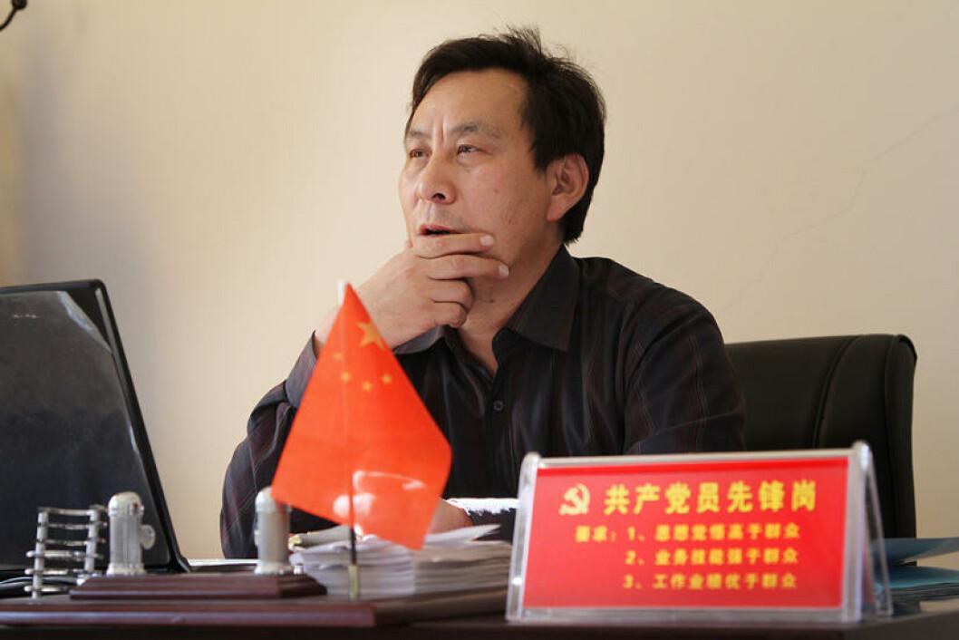 IKKE SOM FOLK FLEST: En god kommunist har høyere moral, jobber hardere og er mer kompetent, forteller skiltet sjefen Wang Yansheng har på pulten. Foto: Kristoffer Egeberg