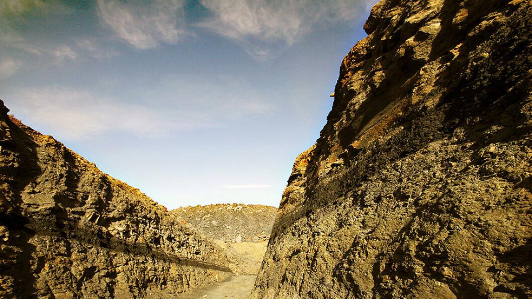 STORE FOREKOMSTER: Det sorte gullet ligger i 17 lag nedover i fjellet ved Wuhushan-gruven. De to øverste lagene ligger nesten helt oppe i dagen, og kan ses som sorte streker på bildet. Foto: Kristoffer Egeberg