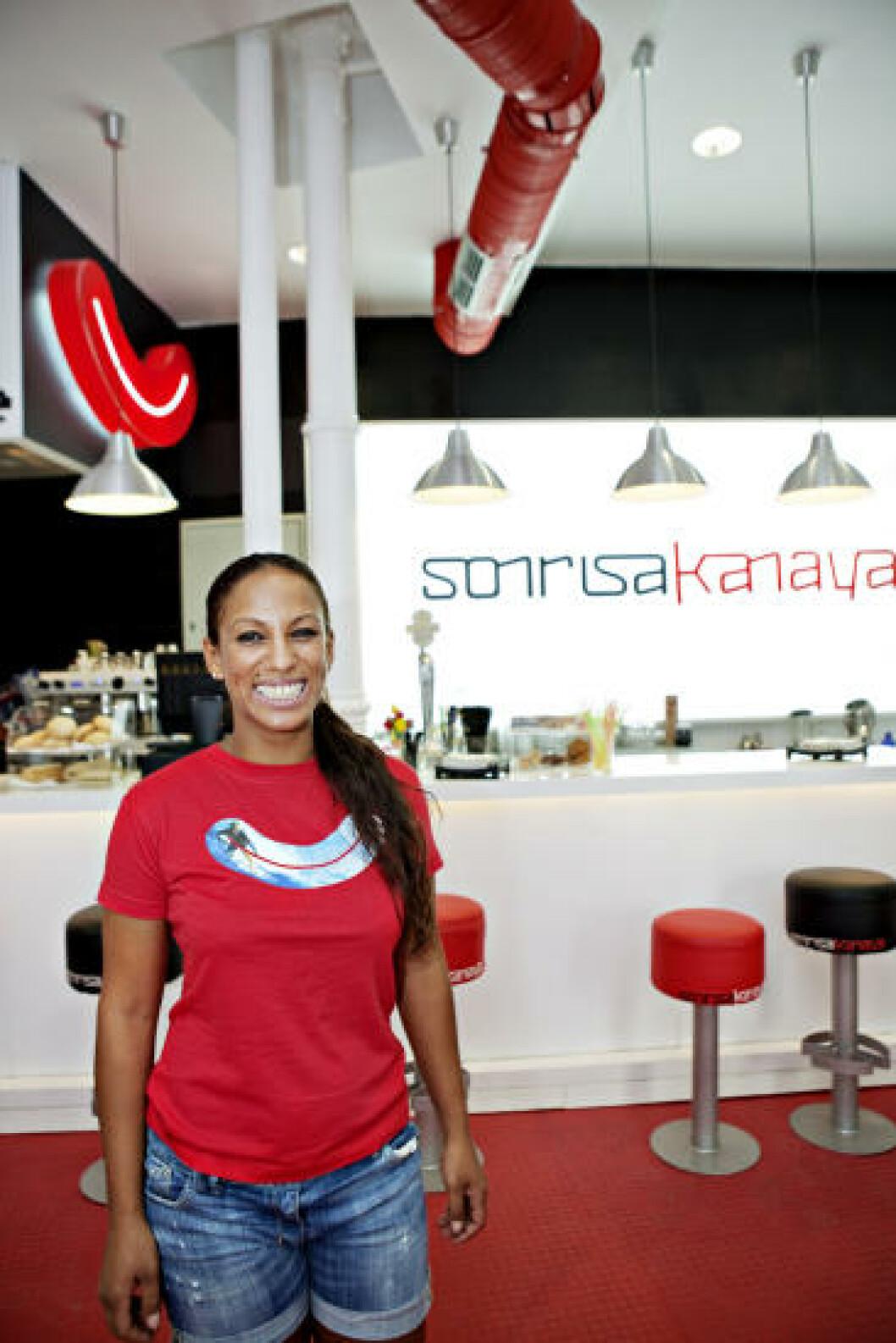 SMIL: Kafeen med klesbutikk heter «Smil». Servitør og ekspeditør Marias Santos fra Brasil følger godt opp. Foto: NINA HANSEN
