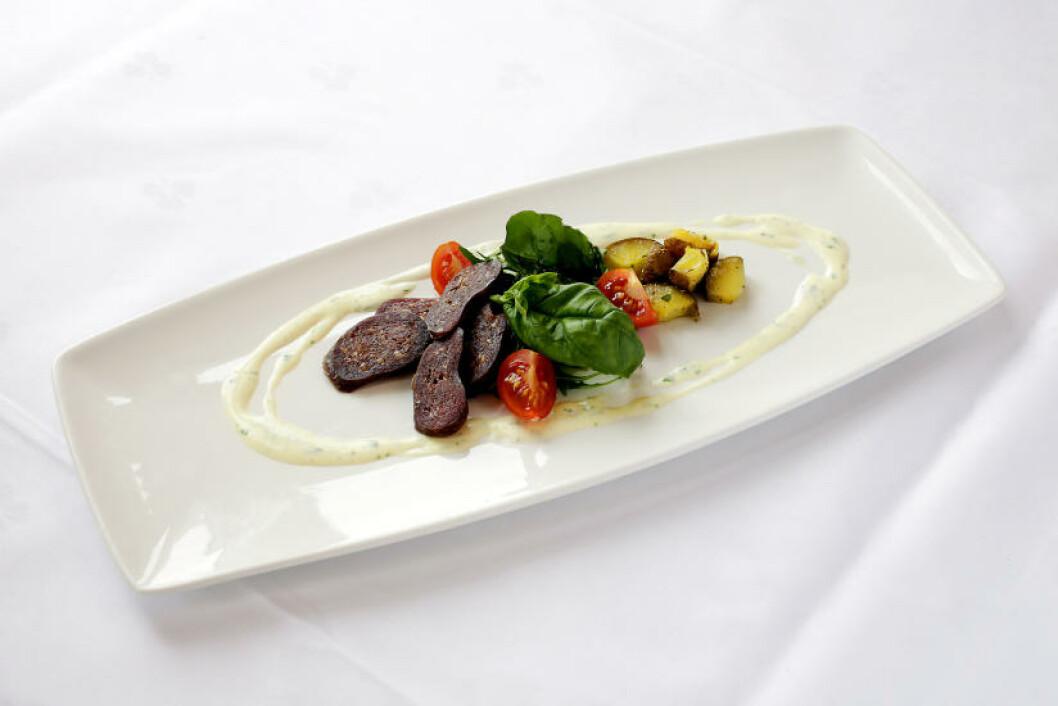 <strong>FORRETT:</strong> Morrpølse laget av lokal villhjort servert med med salat av mandelpoteter. Foto: OLE C. H. THOMASSEN