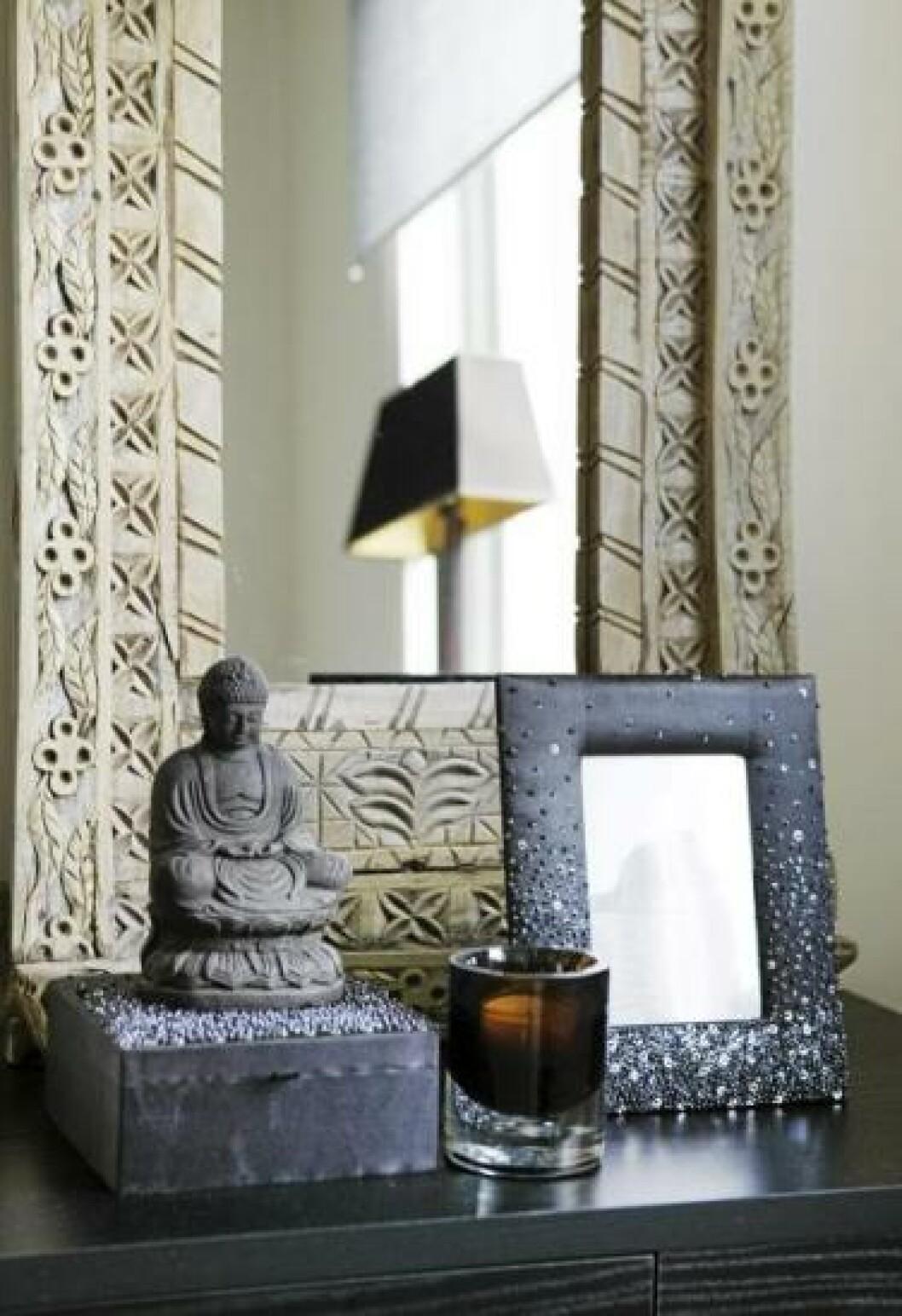 <strong>ØSTENS MYSTIKK:</strong> Buddahfiguren og det indiske speilet med utskjæringer tilfører et østlig preg til soverommet. Speilet fra India finnes hos Anouska. Boksen og rammen med paljetter er fra samme sted. Styling: Tone Kroken. Foto: Yvonne Wilhelmsen