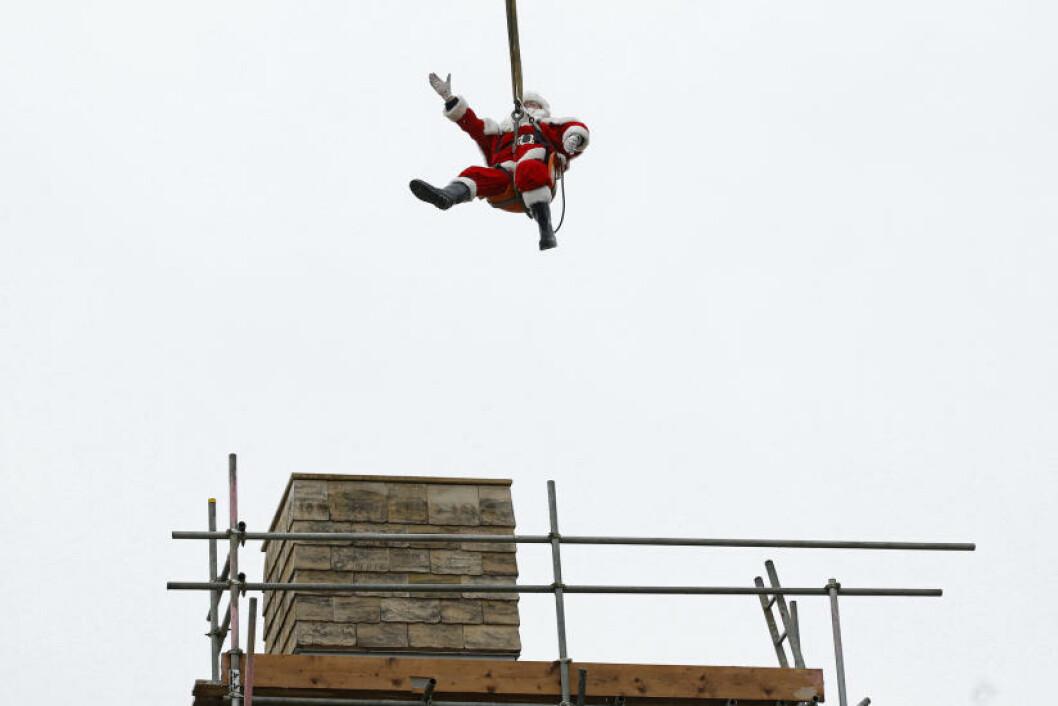 <strong>I SITT RETTE ELEMENT:</strong> Her er endelig nissen slik vi kjenner ham best, på vei ned i pipa. Foto: STEFAN WERMUTH/REUTERS