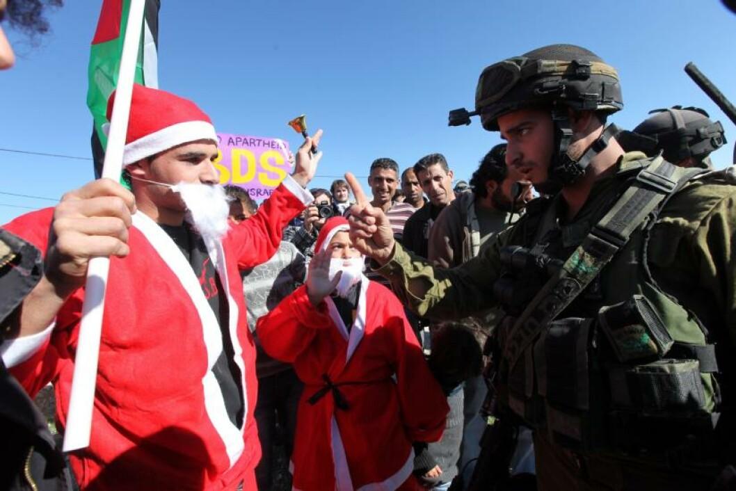 <strong>VED BETLEHEM:</strong> En palestinsk mann har tatt på seg nissedrakta i en demonstrasjon mot Israel i Maasarah ved Betlehem. Foto: ABED AL HASHLAMOUN/EPA