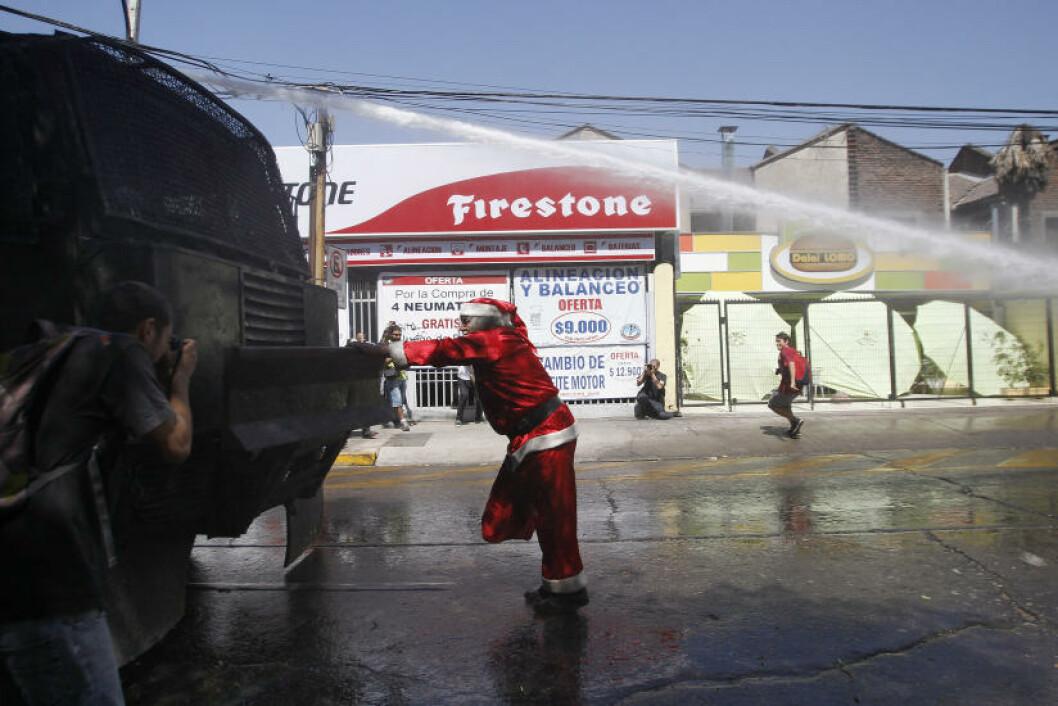 <strong>SINNA I SANTIAGO:</strong> En demonstrant har kledd på seg nissedrakt i chilenske Santiago. Det hjalp lite. Politiet lot ham lilkevel ikke holde på som han ville. Foto: IVAN ALVARADO/REUTERS