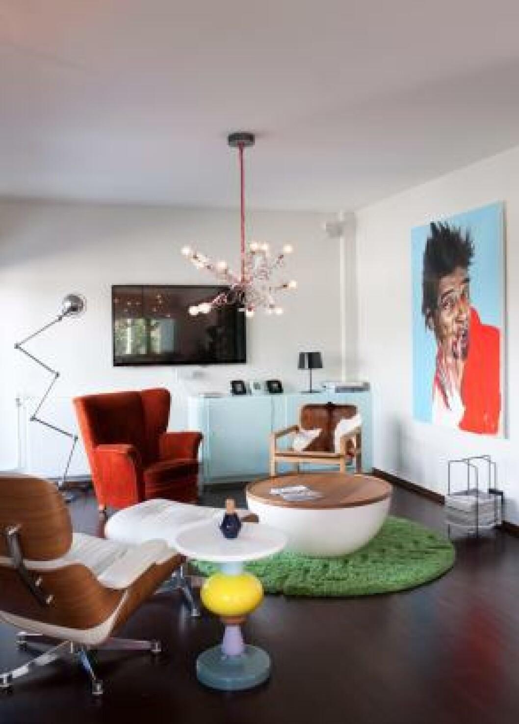 <strong>SOFALØS STUE:</strong> Stua er innredet med en uvanlig møbelmiks: Eames Lounge Chair fra Vitra, Shuffle sidebord fra Andtradition, bord med oppbevaringsplass fra Bolia, en gammel ørelappstol og en enkel hvilestol fra R.O.O.M. kledd med kuskinn fra Ikea. Gulvteppet er fra Permafrost, taklampa fra Ingo Maurer. Bildet er malt av Kristoffer Evang. Flatskjermen er nesten borte i vrimmelen. Foto: Espen Grønli