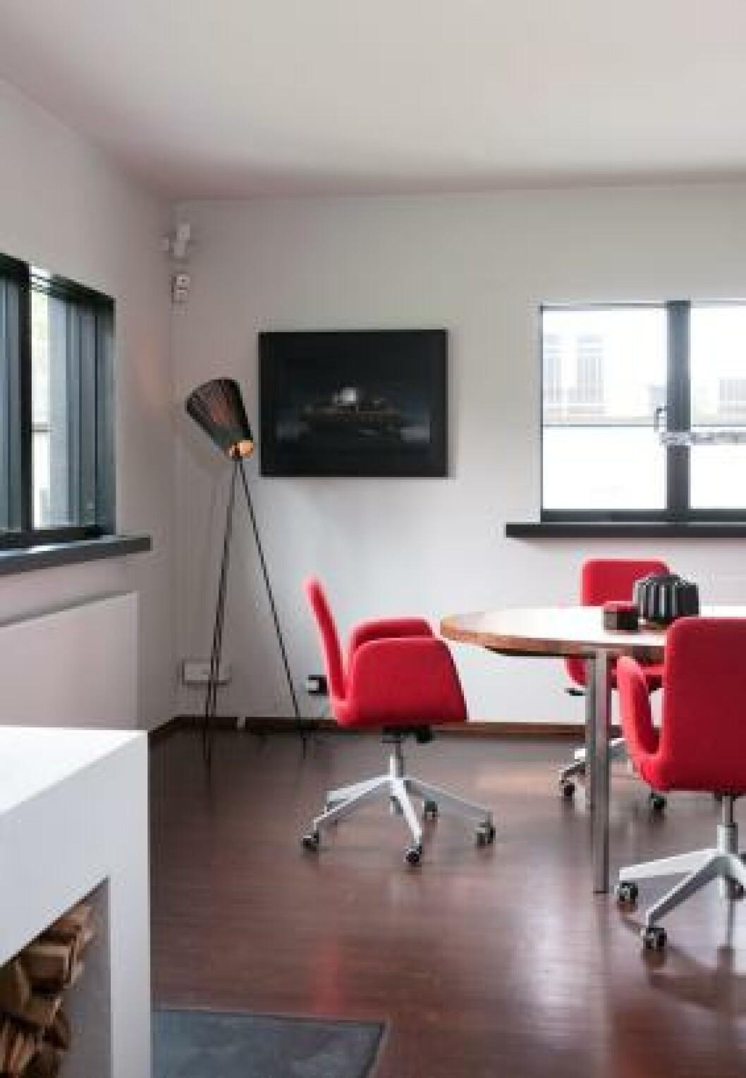 <strong>MØBLERT SOM MØTEROM:</strong> Spisestua kan ligne et møterom på grunn av de røde svingstolene fra Ikea. Foto: Espen Grønli